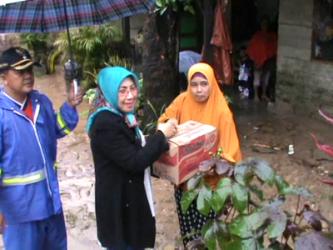 Hj Normadia Mansur Masie Abunawas memberikan bantuan makanan dan minum kepada korban banjir di kelurahan Kampung salo. FOTO : FA
