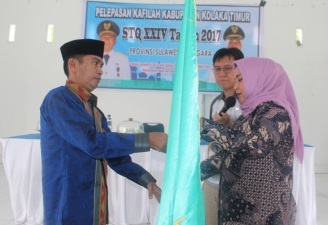 Wakil Bupati Koltim Hj Andi Merya Nur menyerahkan pataka kepada ketua tim rombongan Kafilah MTQ dan disaksikan Asisten III Syamsul Madjid. FOTO : JUSRAN