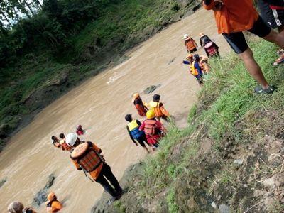 Tim SAR bersama warga saat menyusuri sungai untuk melakukan pencarian korban yang terseret arus sungai. FOTO : BISMA SURYA KURNIAWAN