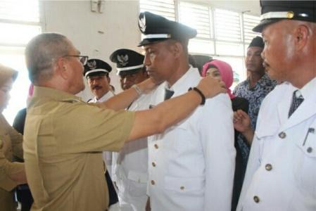 Bupati Kolaka Timur Drs H Tony Herbiansyah MSi, menymatkan tanda pangkat pada salah satu lurah yang dilantik bersama ratusan pejabat eselon Empat. FOTO : JUSRAN
