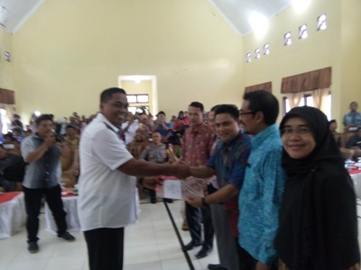 Ketua KIP Aceh Singkil Yarwin Adi Dharma menyerahkan berkas berita acara, kepada bupati Aceh Singkil terpilih Dulmusrid Kamis(6/4) di gedung serbaguna pulosarok. FOTO : MAN