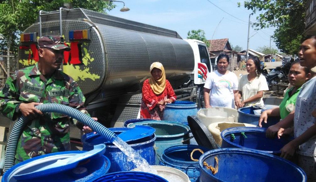 Anggota TNI saat membagikan air kepada Warga RT 3 dan RT 5 Desa Kedung Malang, Kecamatan Kedung, Kabupaten jepara. FOTO : DSW