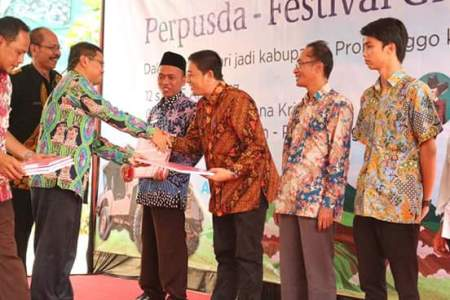Asisten Administrasi, Ekonomi dan Pembangunan Kabupaten Probolinggo, Ir. Anung Widiarto, MM saat menyerahkan buku kepada sejumlah peserta yang hadir dalam pameran buku di Probolinggo. FOTO : ASL