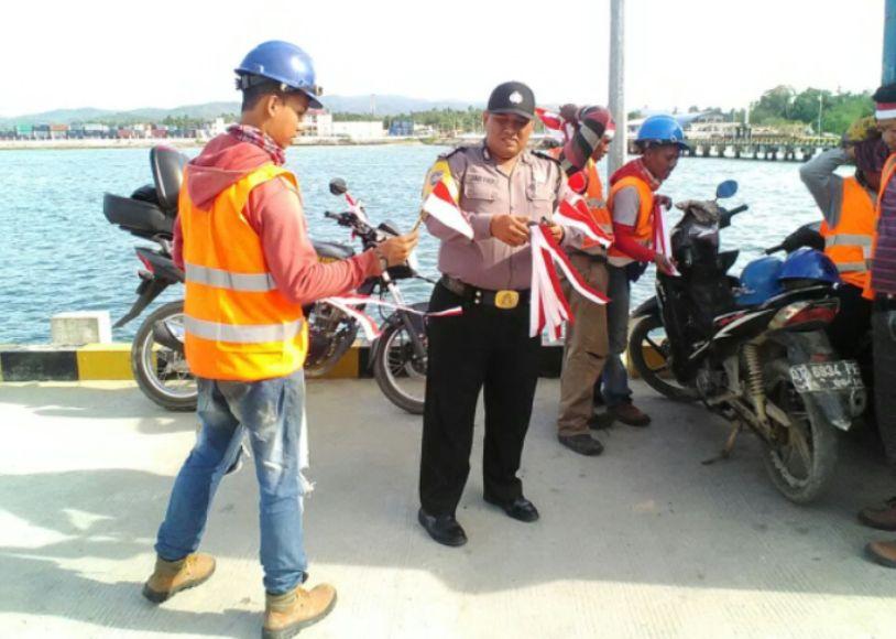 Anggota Kepolisian KP3 membagikan souvenir bendera kepada setiap warga di kawasan pelabuhan nusantara. FOTO : ONNO