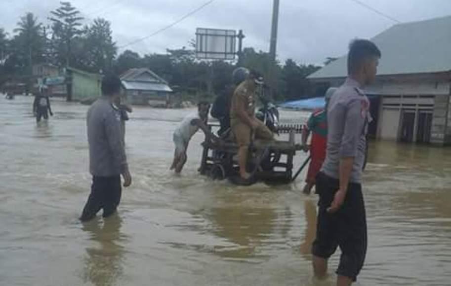 Banjir yang melanda di wilayah Konawe Selatan, khususnya di Laeya . Tampak seorang PNS menggunakan jasa ojek untuk melakukan penyebrangan. FOTO : MAHIDIN