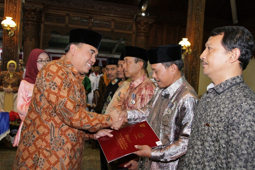 Bupati jepara Ahmad Marzuki saat menyerahkan Satyalencana karya kepada perwakilan PNS penerima penghargaan. FOTO : DSW