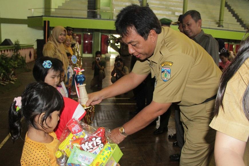 Sekretaris Daerah (Sekda) Ir. Sholih, MM saat menyerahkan sebuah tropy kepada salah satu anak yang menjadi pemenang lomba di Hari Anak Nasional. FOTO : DSW