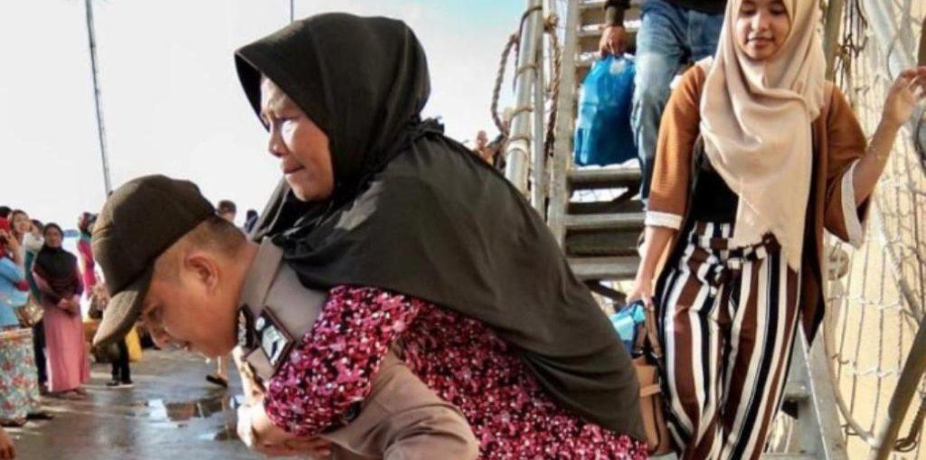 Berita Foto: Brigadir Alimuddin Gendong Emak – Emak Turun Kapal