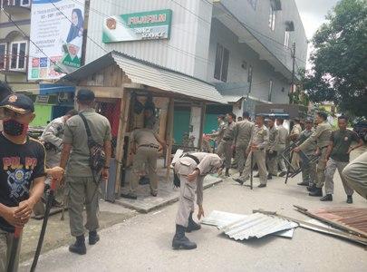 satpol PP saat membongkar kios warga yang dianggap melanggar perda. FOTO : FT