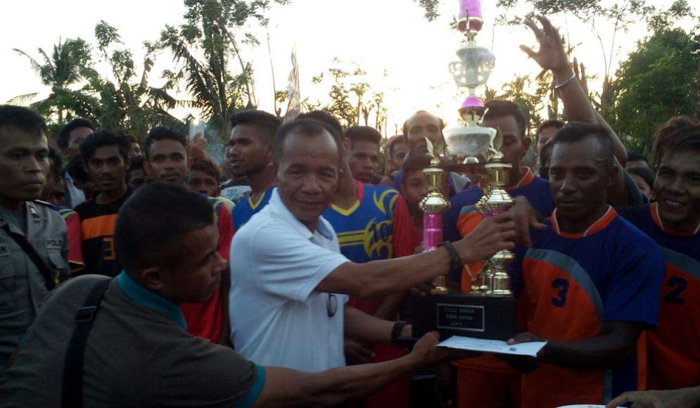 Sekretaris Daerah Kabupaten Muna Nurdin Pamone (baju putih) saat menyerahkan tropi dan uang pembinaan kepada kapten tim futsal Desa Pure akhir pekan lalu. FOTO : LA ODE AWALUDDIN