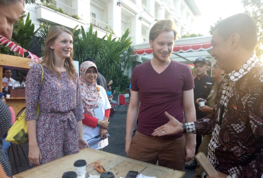 Walikota Yogyakarta Haryadi Suyuti saat berbincang dengan dua turis di festival kopi FOTO : NADHIR ATTAMIMI