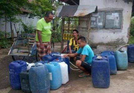 Tampak warga mengisi air bersih di jerigen akibat kekurangan air bersih di sejumlah wilayah yang membuat Pemerintah mengucurkan anggaran Puluhan milyar untuk pasokan air bersih. FOTO : ASL