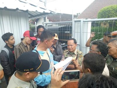 Pemilik lahan bersama satpol PP melakukan diskusi dengan warga setelah melakukan penyegelan. FOTO : NADHIR