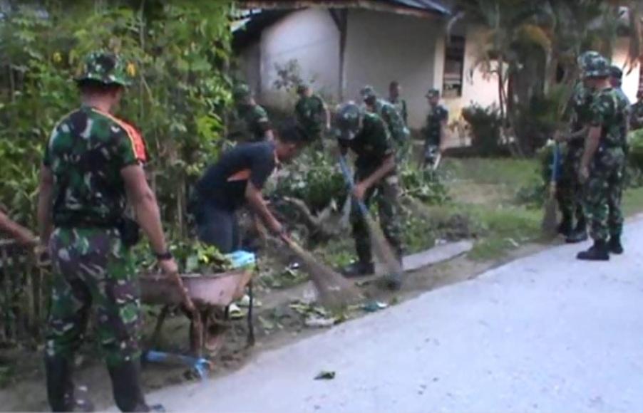 Puluhan anggota TNI dari Unit Zibang saat menggelar bersih-bersih lingkungan pasca banjir di kelurahan kampung Salo. FOTO ; FEBRI