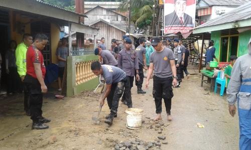 Anggota Kepolisian Polda Sultra membantu warga membersihkan pemukiman warga dari sisa banjir di jalan Lasono Kelurahan Sanua. FOTO : ODEK